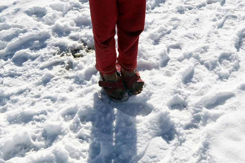 This refugee kid wore only slippers in winter as he didn't have any aid given.
